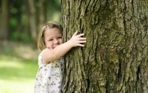 go green, eco friendly renovation tips. Child hugging a tree
